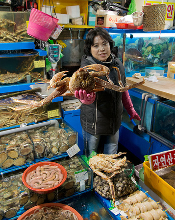 Fish market stall holder with crab